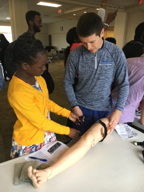 BU alum and current BMC resident Captain Yevgeniy Maksimenko, MD teaches military tourniquet skills to a student from the Boston Area Health Education Center.