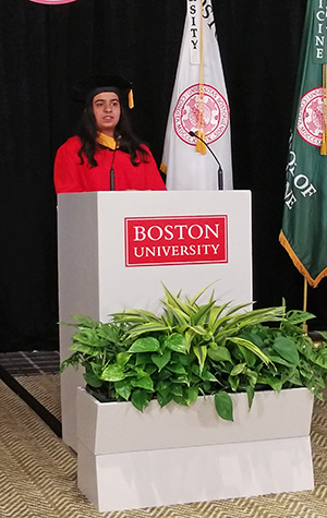 Reshma Gheevarghese in red robe behind white podium giving her address.