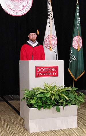 Stephen Wright in red robe behind white podium giving commencement speech