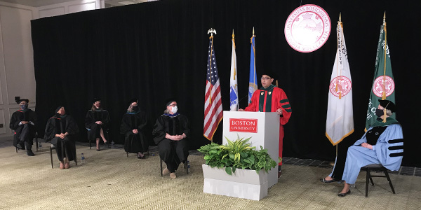 Carlo Pasco in red robe at white podium giving speech surounded by masked faculty seated in a physically distanced manner