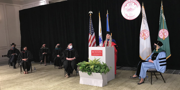 Samantha Shelton in red robe behind white podium giving her speech surrounded by masked faculty seated physically distanced