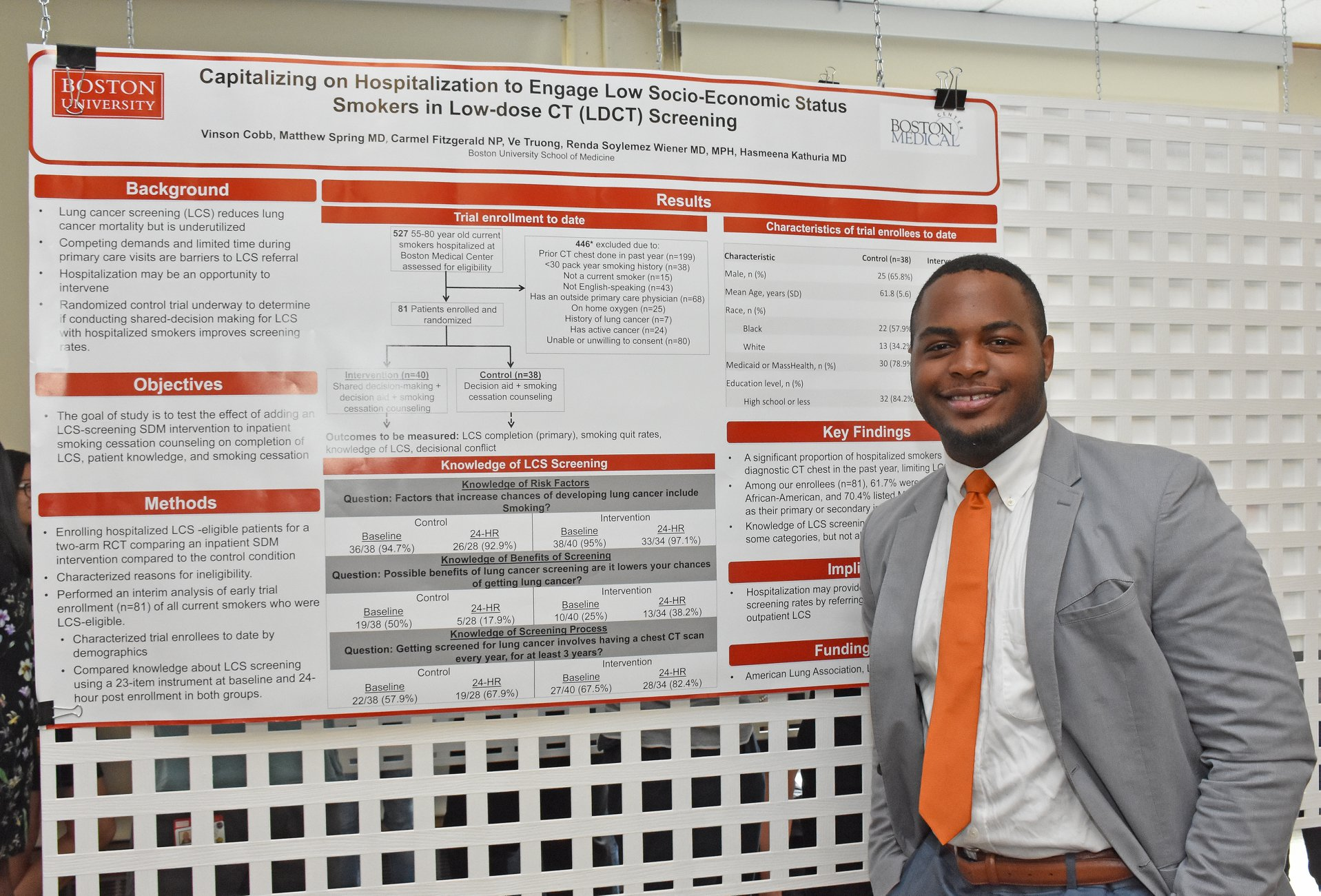 man posing in front of his research poster