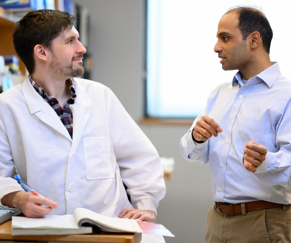 Researchers conversing in lab